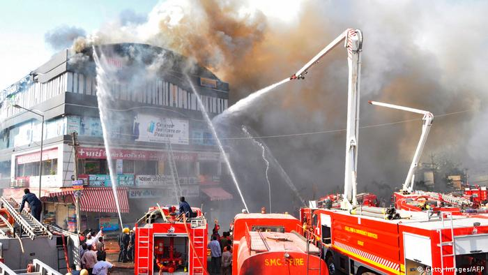 Indian firefighters try to control a major fire in a building housing a college in Surat