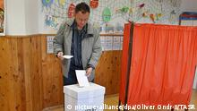 A man places his vote in the ballot box
