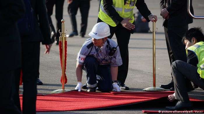 Japanese workers roll out a red carpet for Trump before his arrival at Tokyo's Haneda International Airport