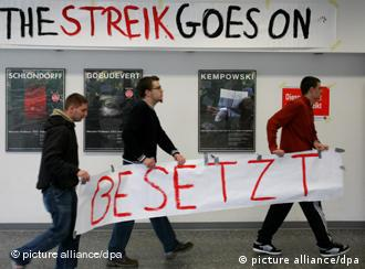 Three students carry a banner under a sign that says The Streik Goes On