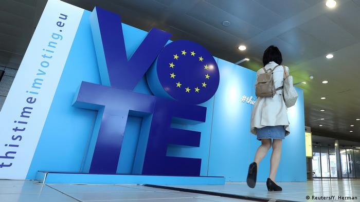 A woman walks past an advertising board for the EU elections near the European Parliament in Brussels