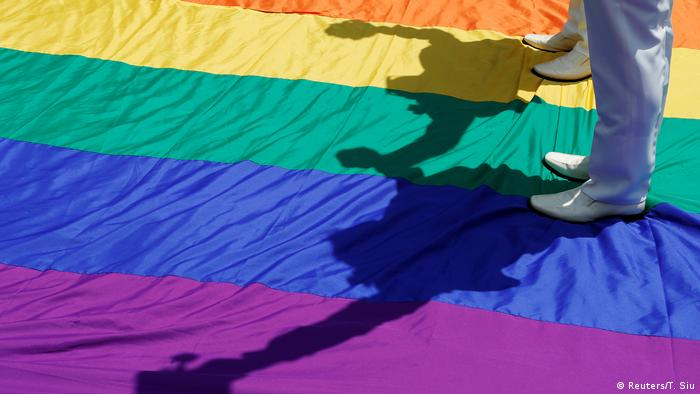 Gay newlyweds walk on a giant rainbow flag