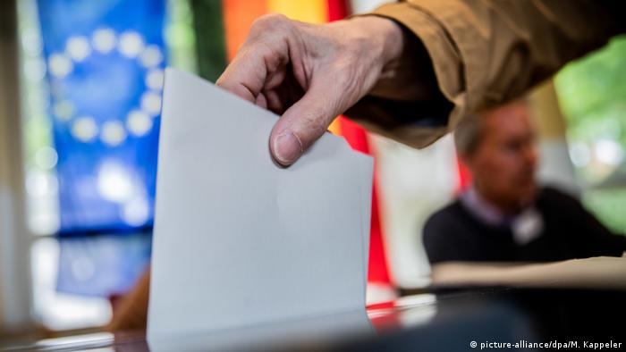Рука, опускающая бюллетень в избирательную урну