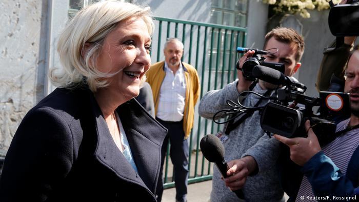 French far-right National Rally party leader Marine Le Pen talks to the media after casting her ballot during the European Parliament Elections, in Henin-Beaumon