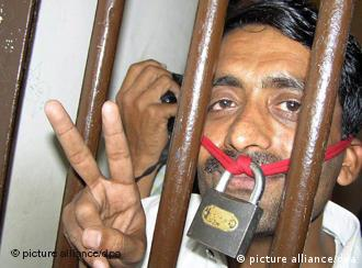 A Pakistani journalist flashes victory signs from inside the lockup of a police station