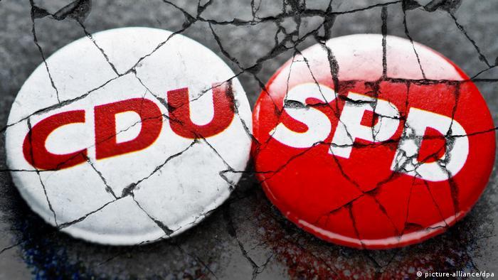 Anstecker der Volksparteien CDU und SPD auf brüchigem Grund