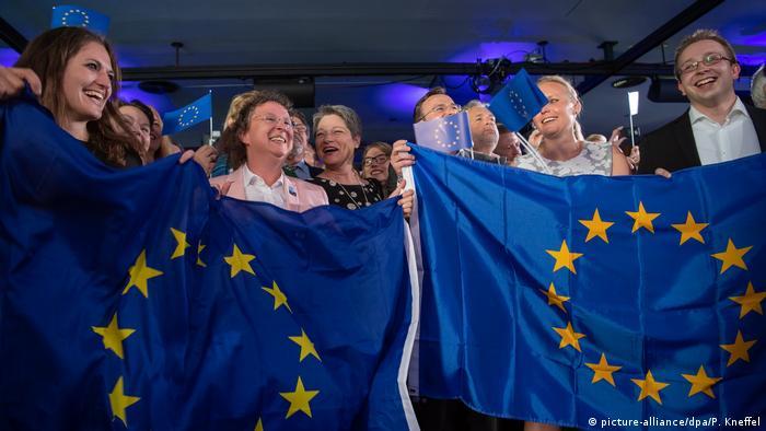 Cidadãos sorridentes portam duas bandeiras da União Europeia