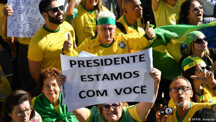 Manifestantes com camisetas amarelas agitam bandeiras do Brasil. Uma delas levanta cartaz com dizeres Presidente Estamos com Você
