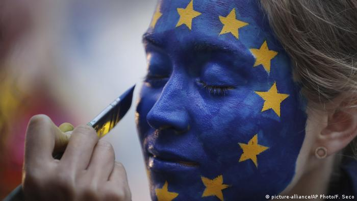 A woman has her face painted with a flag of the European Union