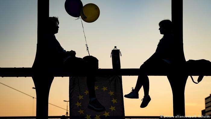 BdTD München Mann und Frau auf Brückenstreben vor Sonnenuntergang