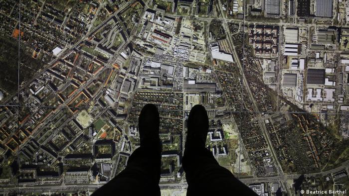 Pés, com sapatos, sobre o grande mapa interativo.