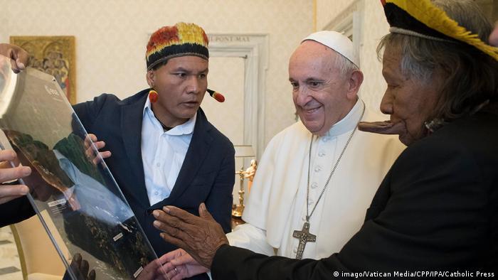 Na foto, líder indígena que vive no Xingu (à esquerda) mostra objeto ao Papa (centro). O cacique Raoni está à direita do pontífice