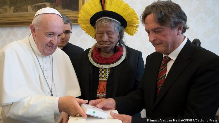 Há três pessoas na foto. Bem à esquerda está Franciso. No meio, está o cacique Raoni, com cocar e traje típico.
