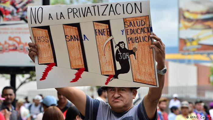 A protester holds up a placard saying 'No to privatization'