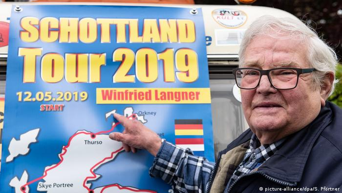 Winifried Langner pointing at a poster which reads 'Scotland Tour 2019' (picture-alliance/dpa/S. Pförtner)