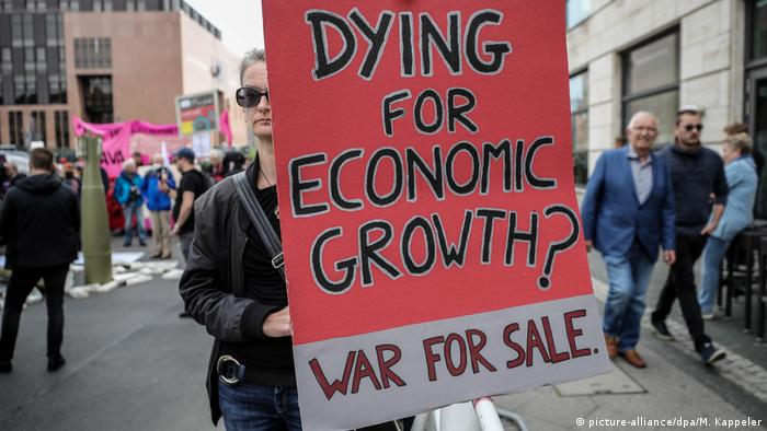A protestor with a sign that reads: 'Dying for economic growth? War for sale'
