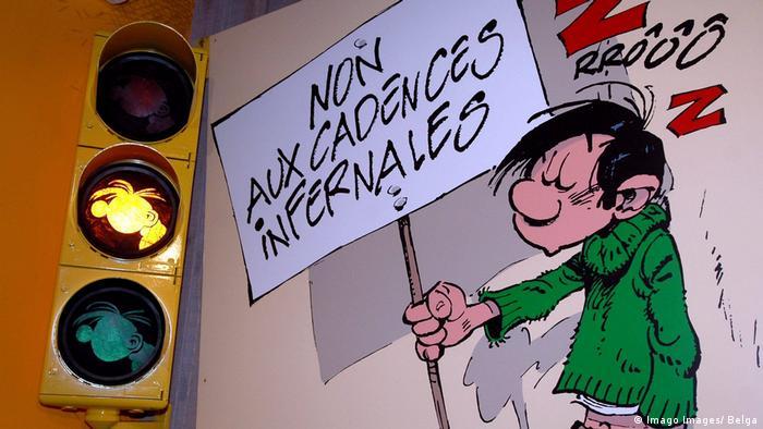 Gaston Lagaffe steht neben einer Ampel mit gelbem Licht und hält ein Plakat hoch (Imago Images/ Belga)