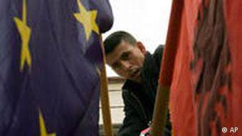 Ethnic Albanian man fixes EU and Albanian flags on a polling station