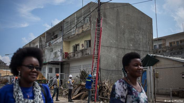 Women walk past a building where electricians are repairing electricity lines (Lena Mucha)