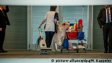 29.05.2019, Berlin: Eine Reinigungskraft schiebt im Kanzleramt ihre Geräte durch den Flur, während Bodyguards danebenstehen. Foto: Michael Kappeler/dpa | Verwendung weltweit