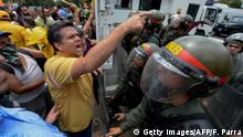 TOPSHOT - Venezuelan opposition deputy Rafael Guzman (L) takes part in a protest against the government of President Nicolas Maduro -blocked by the National Guard- at the Francisco Fajardo highway in Caracas on April 1, 2017. Venezuela's Supreme Court abandoned measures to seize power from the opposition-controlled legislature after the moves drew international condemnation and raised pressure on President Nicolas Maduro. The president of Venezuela's National Assembly Julio Borges dismissed the court's gesture and told reporters that nothing had changed and the coup continued. / AFP PHOTO / FEDERICO PARRA (Photo credit should read FEDERICO PARRA/AFP/Getty Images)