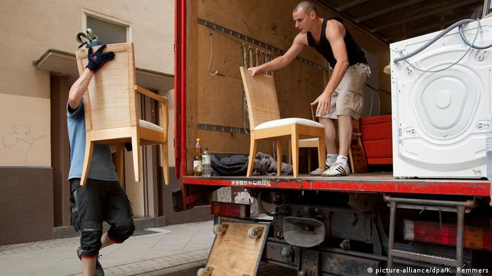 Men move furniture off a truck into a house (picture-alliance/dpa/K. Remmers)