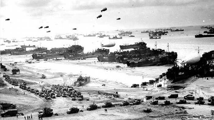 Dezenas de embarcações, veículos e aeronaves militares na costa da Normandia, em 6 de junho de 1944, conhecido como o Dia D
