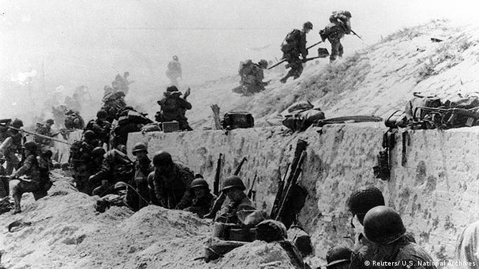 Soldados americanos escalam uma muralha de concreto na Praia de Utah, na Normandia, em 6 de junho de 1944