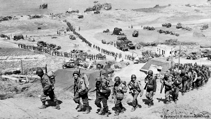 US Army reinforcements march up a hill past a German bunker overlooking Omaha Beach after the D-Day landings near Colleville sur Mer, France, June 18, 1944.