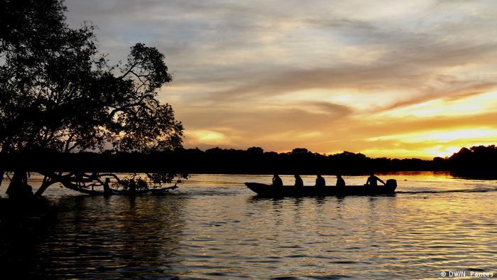 Indígenas em barco no pôr do sol