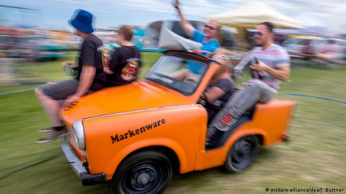 A group of people celebrating in and on an orange Trabi convertible (picture-alliance/dpa/J. Büttner)