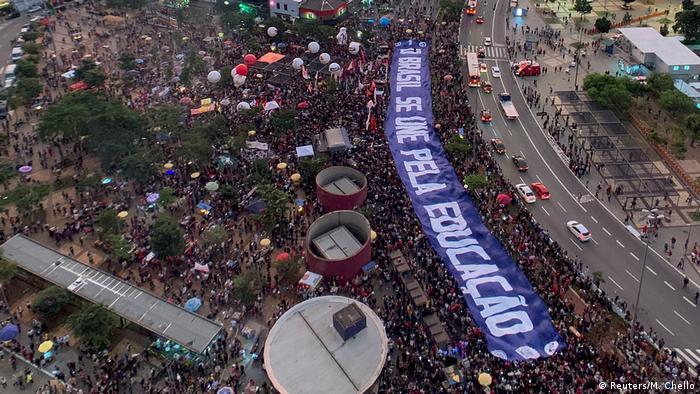 Visão aérea de multidão na rua, segurando faixa gigante com o dizer Brasil se une pela educação