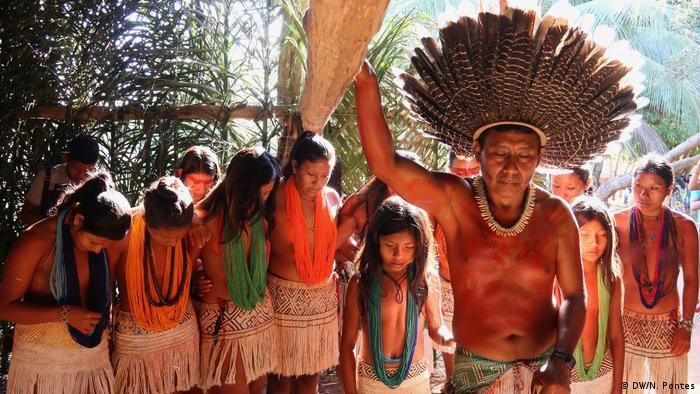 À frente da foto, cacique, com um cocar. Em segundo plano, um grupo de mulheres indígenas, entre elas, crianças.