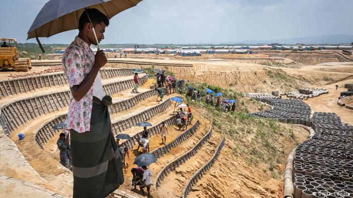A Rohingya refugee looks over a slope that workers are stabilizing with terraces and retention walls in the Kutupalong Camp