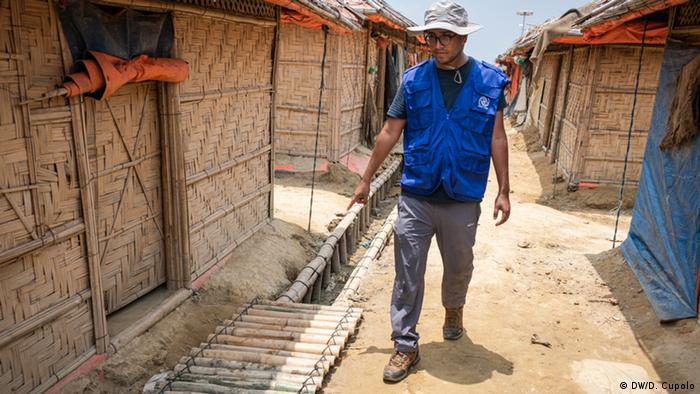 Navin Karki, a site management officer for IOM, points out new drainage ways installed in the camps that should help mitigate rain damage