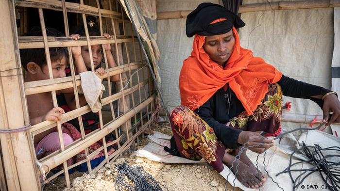 Roshida Begum, a Rohingya mother of four, makes handles for plastic bags that will be used to transport soil as her children look on