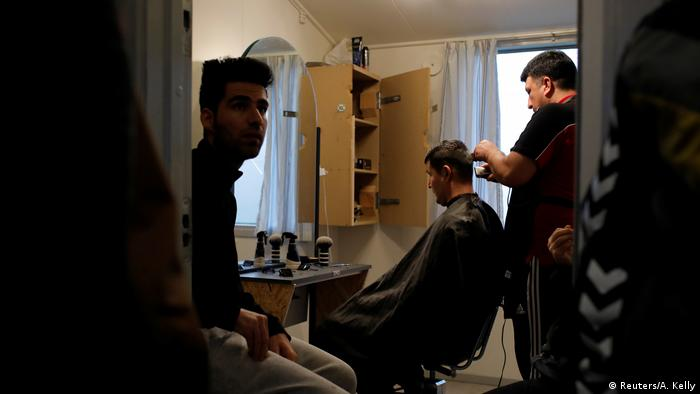 Residents at Kaershovedgaard, a former prison and now a departure centre for rejected asylum seekers, line up to have a free haircut