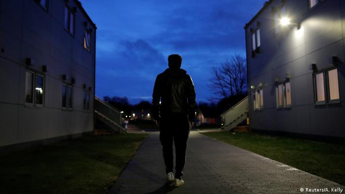 Der Iraner Hoshang Rostami läuft im Dunkeln durch das Abschiebelager Kærshovedgård. Recht uns links von ihm erheben sich weiße Wohnblöcke.