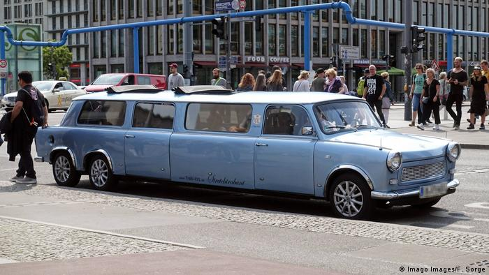 A blue Trabant limo in Berlin sitting next to the curb.
