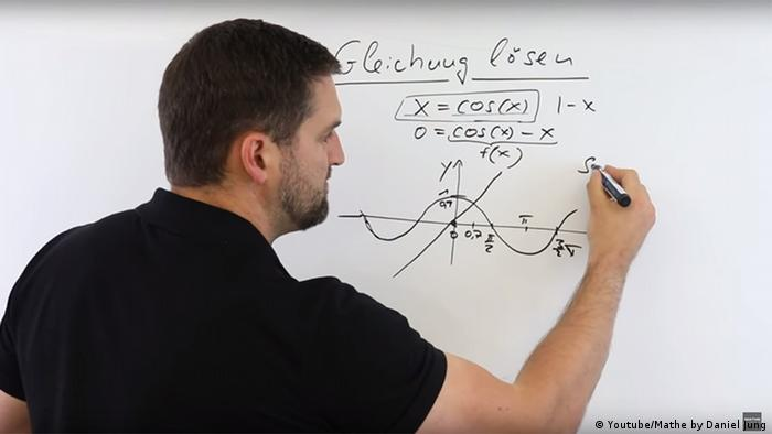 A man doing a calculation on a white board