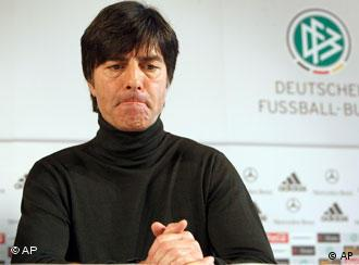 Germany coach Joachim Loew sitting in front of the German Soccer Association's logo