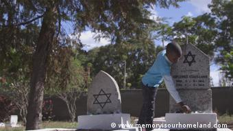 A boy leans over a marble headstone engraved with the Star of David