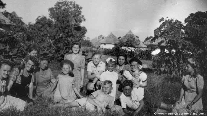 A group of Polish women and children pose for a photo, with African huts visible in the distance behind them