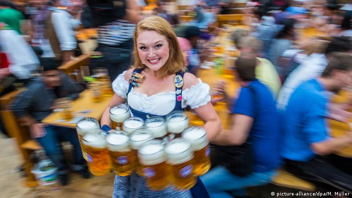 Woman in traditional Bavarian dress serving big filled beer glasses at Munich's Oktoberfest in Bavaria (picture-alliance/dpa/M. Müller)