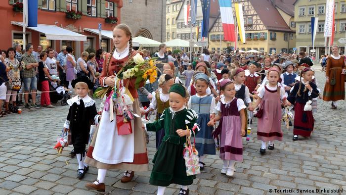 Children in traditional costumes walk in the procession of the Dinkelsbühl Kinderzeche children's feast (Touristik Service Dinkelsbühl)