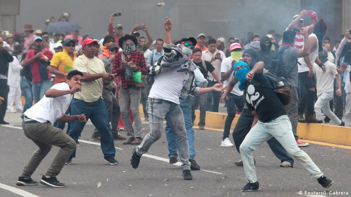 Protesters throw rocks during a demonstration in Tegucigalpa