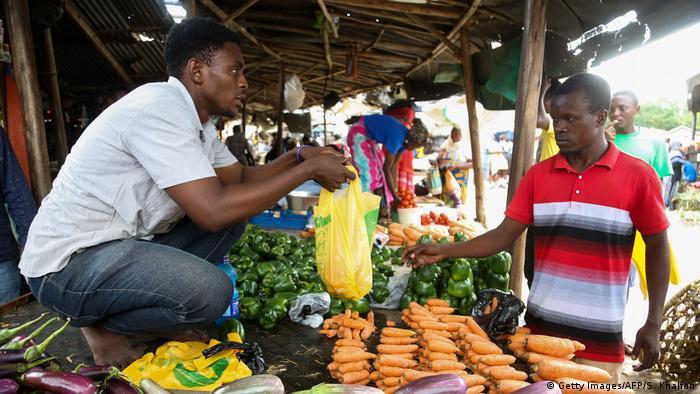 A man using a plastic bag at a market in Dar es Salaam