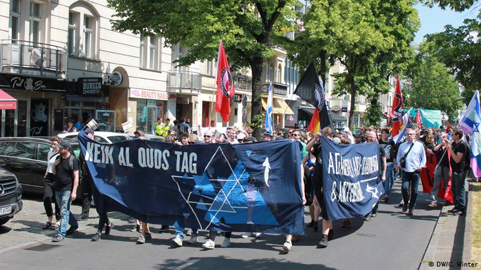 Marchers holding Israeli flags and a banner that reads, in German, No Al Quds Day