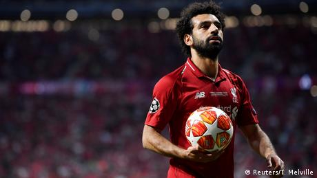 Liverpool's Mohamed Salah holds the UEFA Champions League ball