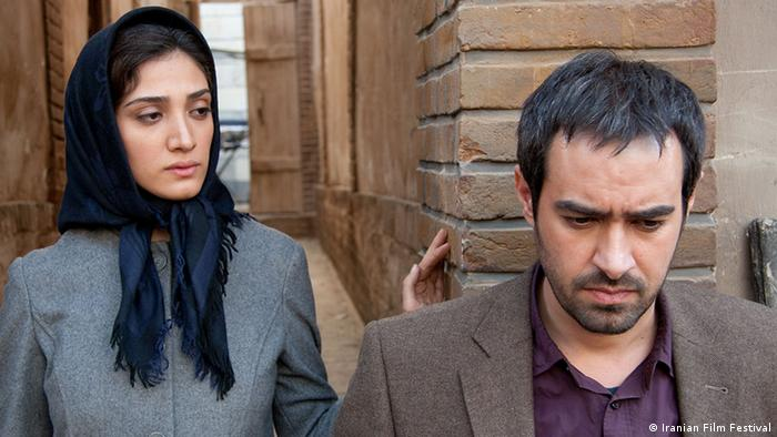 Film still The Paternal House , a woman with a headscarf peers at a man (Iranian Film Festival)